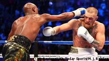 Aug 26, 2017; Las Vegas, NV, USA; Floyd Mayweather Jr. lands a hit on Conor McGregor during a boxing match at T-Mobile Arena. Mandatory Credit: Mark J. Rebilas-USA TODAY Sports