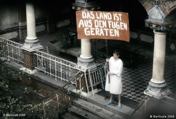 Ein Mann im Nachthemd mit Plakat auf dem steht: Das land ist aus den Fugen geraten