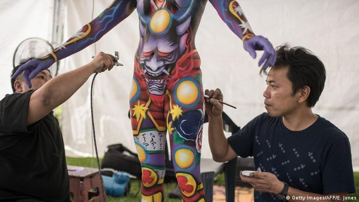 Artist Iwasaki Masakazu (L) of Japan applies spray paint to a model, while another man applies delicate brush strokes.