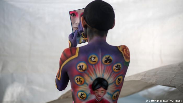 A painted model checks her make-up in a handheld mirror at the Daegu Bodypainting Festival in South Korea.