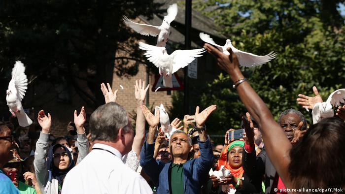 people, hands in the air, white doves (picture-alliance/dpa/Y.Mok)