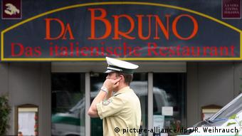 Duisburg policeman on his cell phone before Da Bruno restaurant