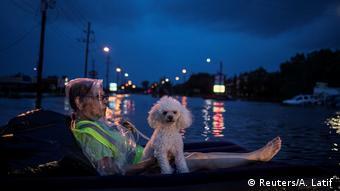 Aposentada e seu cão de estimação aguardam resgate boiando num colchão inflável pelas ruas de Houston
