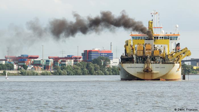 A ship in Hamburg harbour spews black sooty smoke