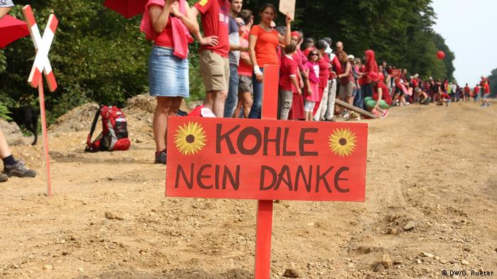 A sign saying coal, no thank you with a crowd of protesters in the background