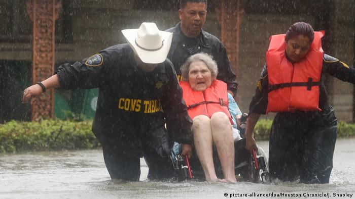 Rescuers helping an elderly woman to safety Jon Shapley/Houston Chronicle/dpa