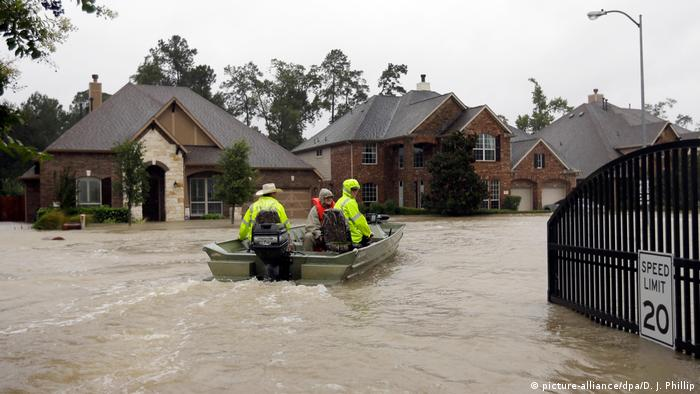 A boat floats down a flooded street in Spring, Texas (picture-alliance/dpa/D. J. Phillip)