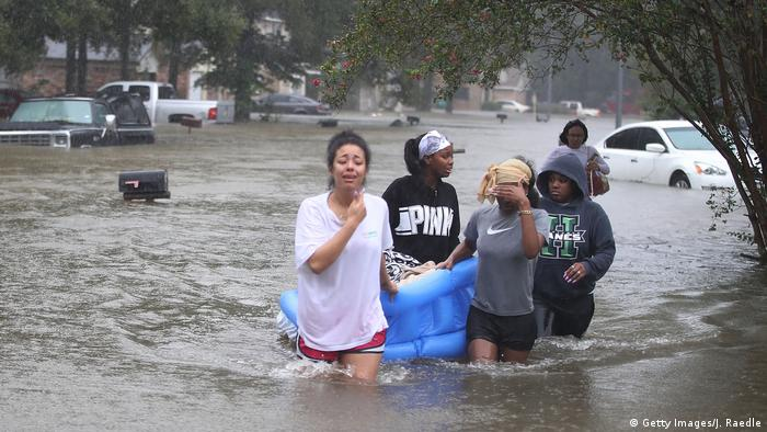 People wading down a flooded street as they evacuate their homes after flooding from Hurricane Harvey on August 28, 2017 in Houston, Texas