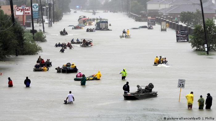 Rescue boats fill a flooded street at flood victims are evacuated as floodwaters from Tropical Storm Harvey