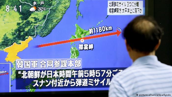 Японец смотрит на телеэкран с картой пролета северокорейской ракеты
