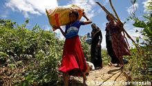 Rohingya people carry their belongings while crossing the Bangladesh-Myanmar border, in Cox's Bazar, Bangladesh, August 27, 2017. REUTERS/Mohammad Ponir Hossain