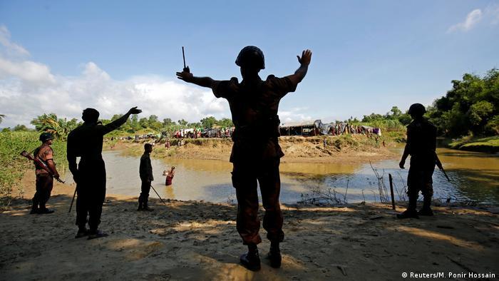 Miembros de la Guardia de Fronteras de Bangladesh (BGB) ordenan a los rohingya que no atraviesen el canal entre Bangladesh y Myanmar.