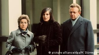 Three people standing outside a house in a film still from The Lost Honor of Katharina Blum