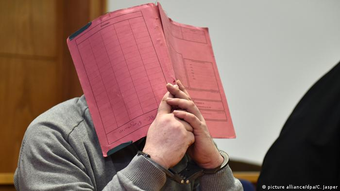 Niels H hiding behind a folder in court