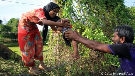 A Rohingya man passes a child though a barbed wire border fence