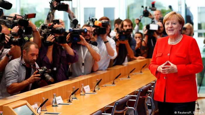 Перед началом Меркель терпеливо позировала фоторепортерам