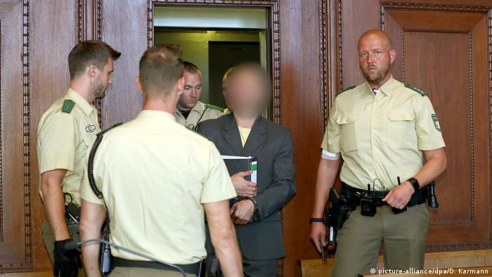 Wolfgang P., pictured with a blurred face, is escorted by guards into a Nuremberg courtroom