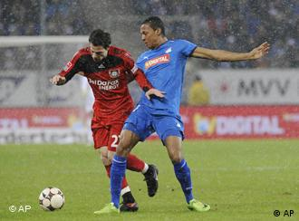 Hoffenheim's Luiz Gustavo, right, challenges for the ball with Leverkusen's Gonzalo Castro