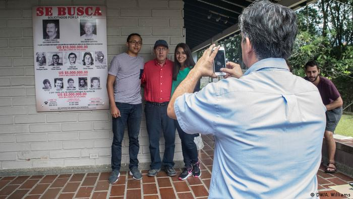 Tour guide Jesus photographs tourists with Roberto Escobar in his house in Medellin