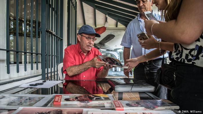 Roberto Escobar signs photos of his brother Pablo Escobar for tourists