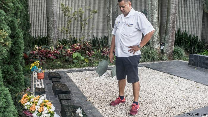 Carlos Palau stands in front of the grave of Pablo Escobar in Medellin