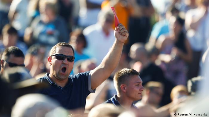 A man shouts and waves a red card during one of Chancellor Merkel's campagin rallies