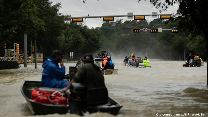 Boats making their way down flooded streets (picture-alliance/AP Photo/G. Bull)