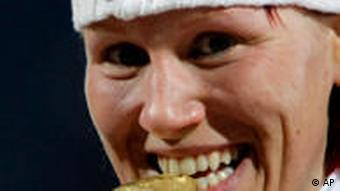 Gold medalist Kati Wilhelm of Germany bites her gold medal during the award ceremony of women's 7.5 km Sprint of the Biathlon World Championships in Pyeongchang, east of Seoul, South Korea, Saturday, Feb. 14, 2009.