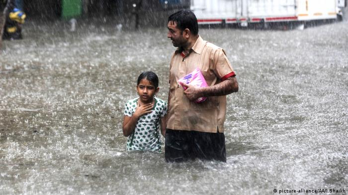 People wade along a flooded street during heavy rain in Mumbai