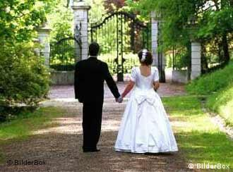 A bride and groom walking along a grassy path, hand in hand