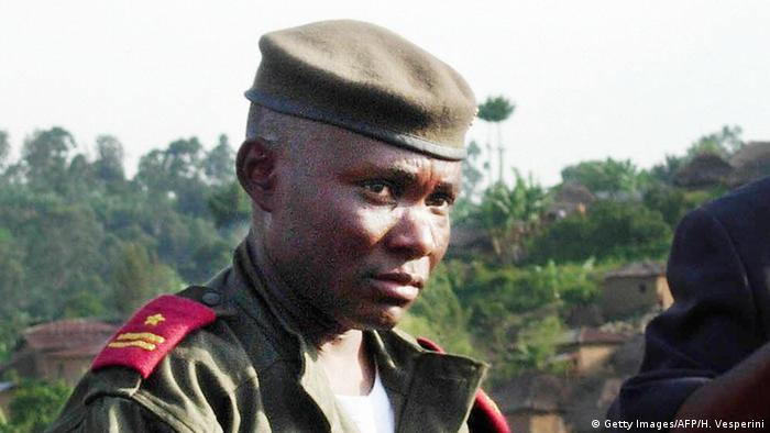 Photo of Amisi wearing a military shirt and beret.