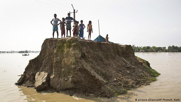 Flood-affected villagers wait for relief material on what's left of a road washed away by floodwaters in Morigaon district, east of Gauhati, northeastern state of Assam (picture-alliance/AP Photo/A. Nath)