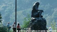 Die Loreley-Statue bei St. Goarshausen. Im Hintergrund Touristinnen und Touristen