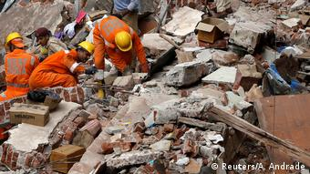 Rescue workers search for survivors at the site of a collapsed building in Mumbai