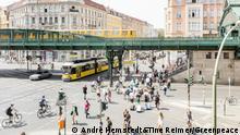 Transportation infrastructure in Berlin. City train, tram, pedestrians and cyclists at a crossing. Oeffentlicher Nahverkehr in Berlin. S-Bahn, Strassenbahn, Fussgaenger und Fahrradfahrer, auf einer Kreuzung.