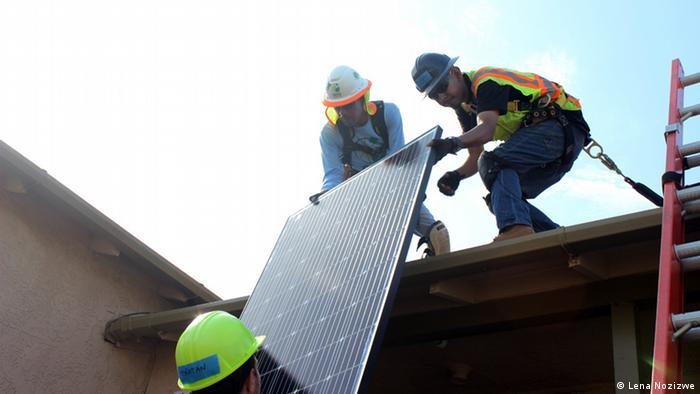 Workers pulling a large solar panel onto a roof