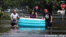 People use an inflatable boat to float their possessions and a dog out of a flooded area of Port Arthur, Texas, U.S., August 31, 2017. REUTERS/Carlo Allegri