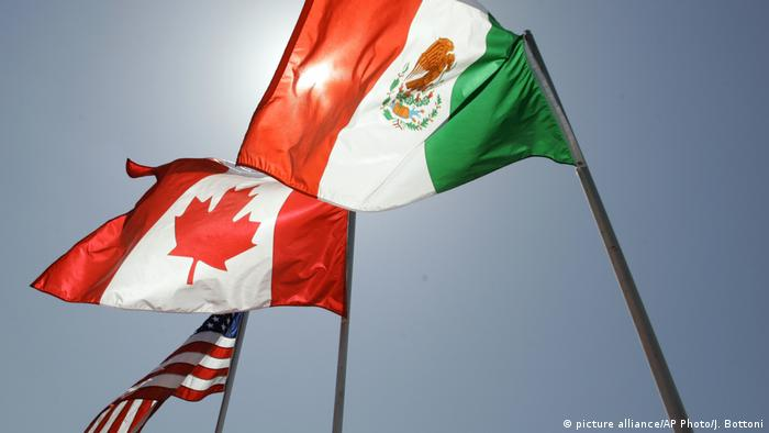 National flags representing the United States, Canada, and Mexico fly in the breeze (picture alliance/AP Photo/J. Bottoni)