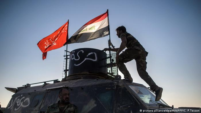 A Shiite fighter stands on an armored vehicle in the airport of Tal Afar
