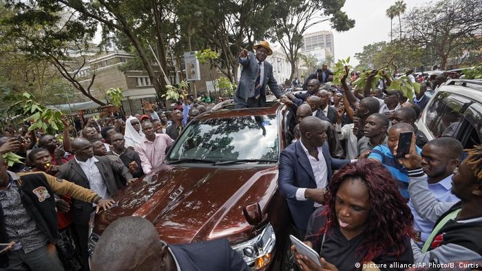 Odinga stands through the roof of a car surrounded by a cheering crowd