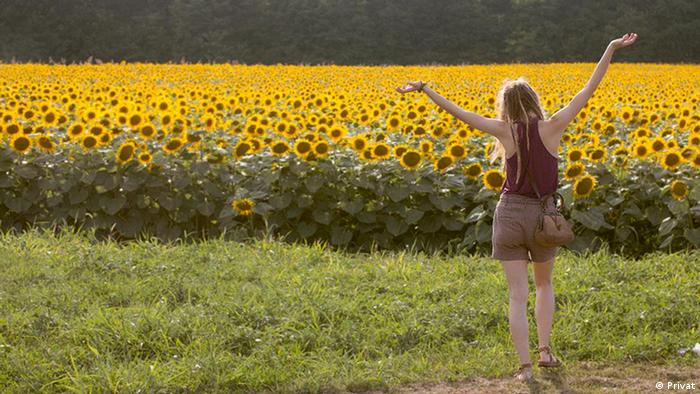 Junge Frau am Sonnenblumenfeld