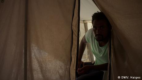 Ο Άμαν από την Ερυθραία ζητά συγγνώμη γιατί δεν μπορεί να προσφέρει τσάι ή νερό στον επισκέπτη του. Ήρθε στη Λέσβο πριν από τρεις μήνες και από τότε περιμένει να εκδοθεί η απόφαση σχετικά με την παροχή ασύλου. «Υπάρχουν πάρα πολλά προβλήματα στο κέντρο της Μόριας» δηλώνει. Ο συνωστισμός και οι εντάσεις μεταξύ διαφόρων ομάδων οδηγούν συχνά σε συγκρούσεις.