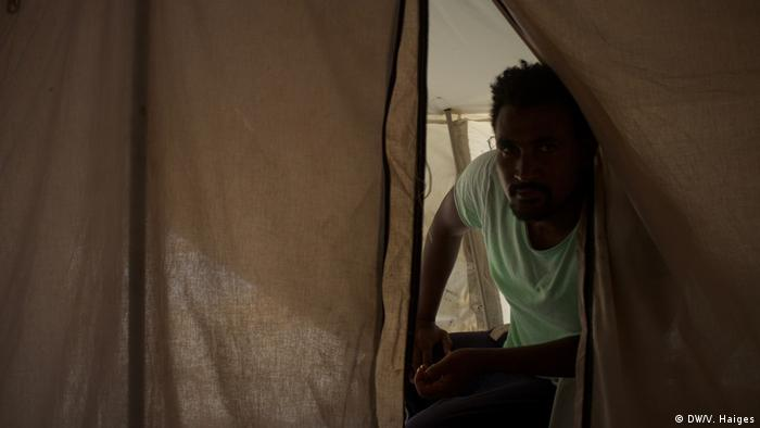 An Ethiopian asylum-seekers peers out of a tent in Lesbos