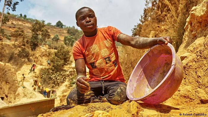 a man pours gold-colored liquid from plastic pan (Robert Carrubba)