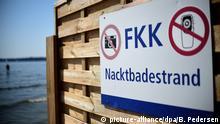 Das FKK-Schild im Standbad Wannsee in Berlin weist auf den Nacktbadestrand hinter dem Sichtschutz hin (Aufnahme vom 17.07.2015). Foto: Britta Pedersen/dpa (zu dpa «Zahl der Nacktbader in Berlin nimmt ab» vom 18.07.2015) | Verwendung weltweit