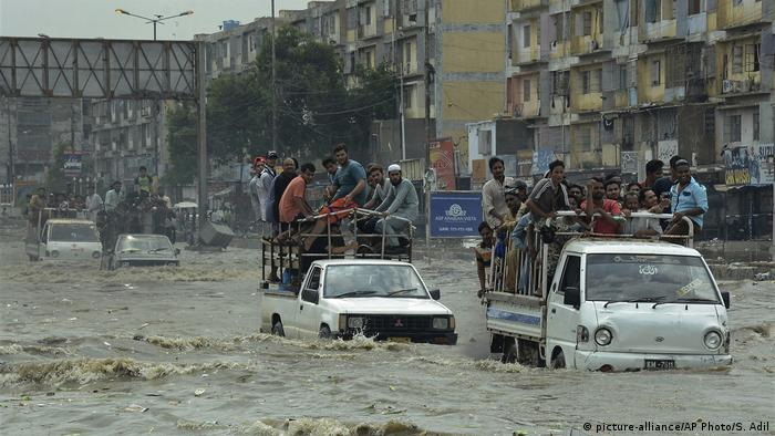 A street scene in the Pakistan capital, Karachi, showing flooding and cars driving through water.