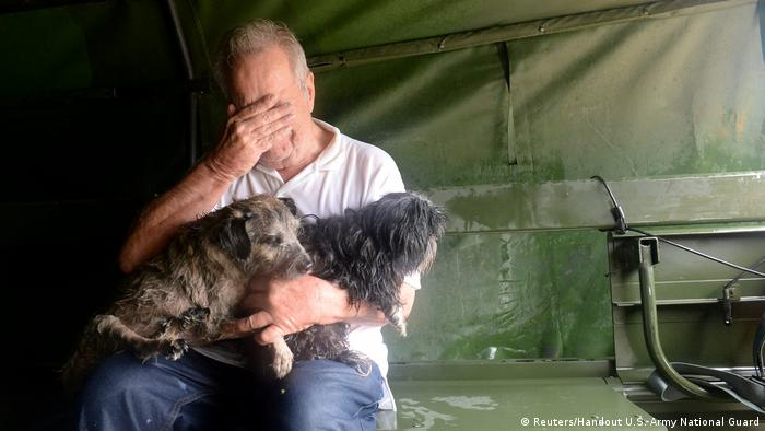 An evacuee holding two dogs reacts after his rescue by Texas National Guardsmen from severe flooding due to Hurricane Harvey