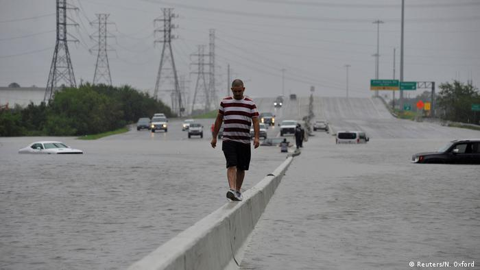 A stranded motorist escapes floodwaters on Interstate 225 after Hurricane Harvey inundated the Texas Gulf coast with rain