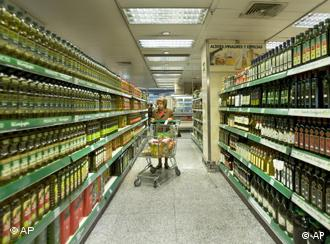 A woman pushes a shopping trolley through a supermarket in Madrid, Spain