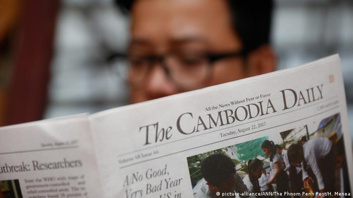 A man read The Cambodia Daily after the publication was threatened by authorities with tax bill amounting to millions of dollars